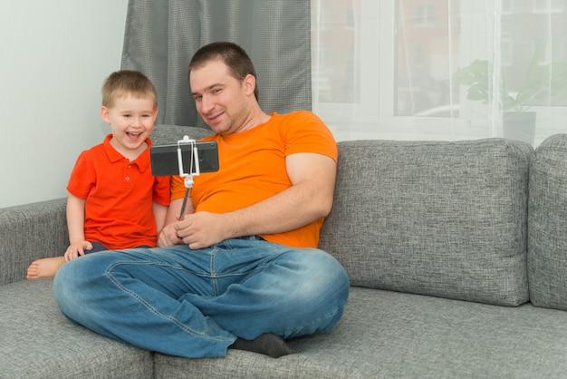 Jongen en man in lichte kleding kijken in de smartphone tijdens online bellen en glimlachen