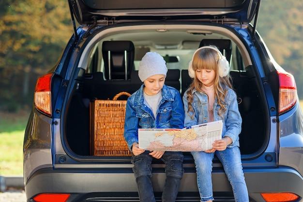 Jongen en meisje bekijken de wegenkaart zittend in de kofferbak van de auto