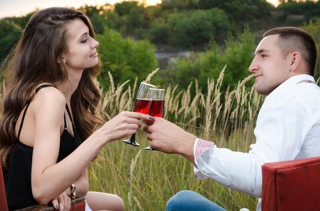 Jongen en meisje die buiten wijn drinken