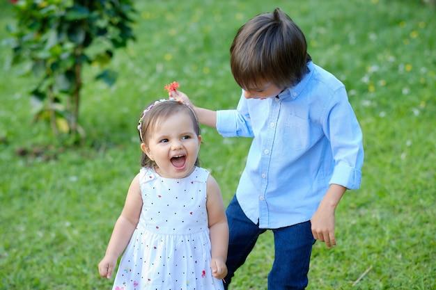 Jongen en meisje die door een groene weide lopen, zien er erg blij uit en glimlachen.