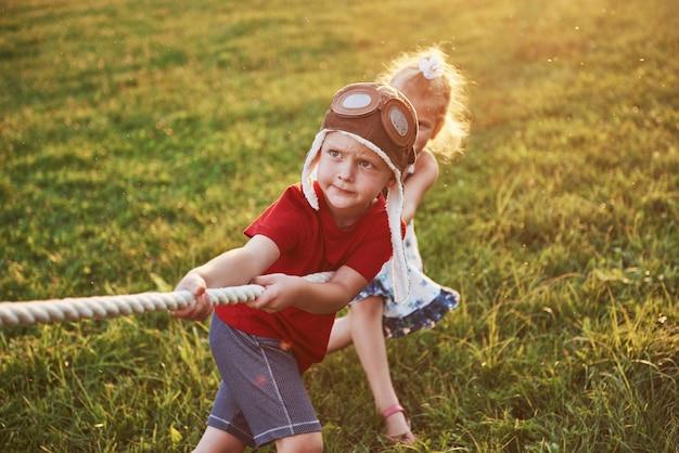 Jongen en meisje die een kabel trekken en touwtrekwedstrijd spelen bij het park
