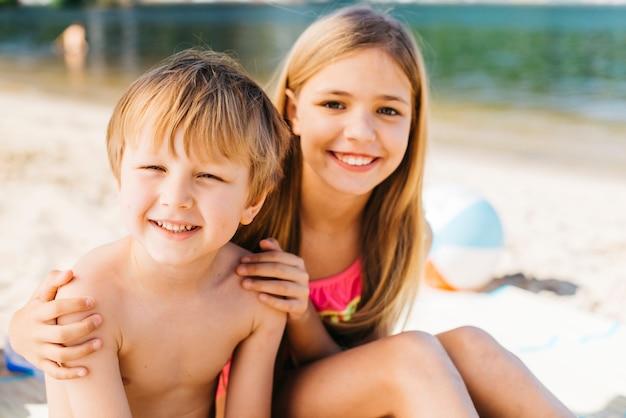 Jongen en meisje die gelukkig bij kust grijnzen
