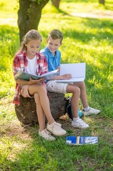 Jongen en meisje die lessen in park doen
