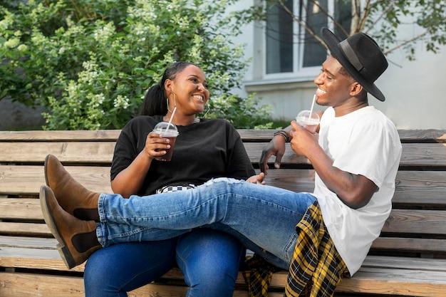 Jongen en meisje die samen van wat smoothies genieten