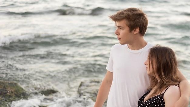 Jongen en meisje die weg op het strand met exemplaarruimte kijken