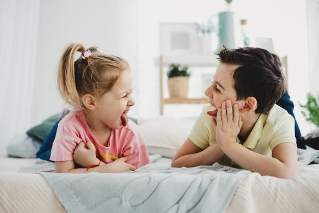Jongen en meisje grimassen naar elkaar liggend op het bed
