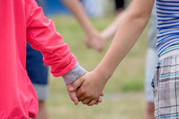 Jongen en meisje hand in hand tijdens het spelen. concept van eenheid en vertrouwen