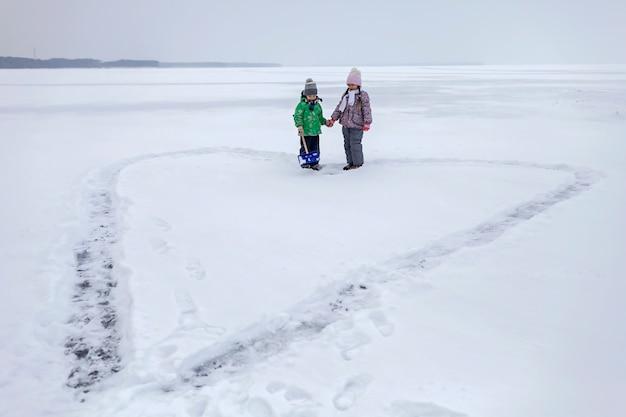 Jongen en meisje hebben plezier en sneeuw verwijderen uit het ijs op het bevroren meer in hartvorm