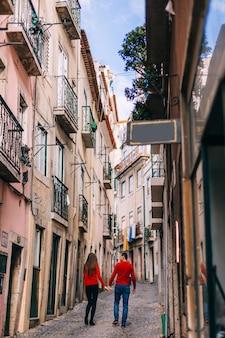 Jongen en meisje houden elkaars hand vast en lopen op de smalle straat in de stad. gebouwen met smalle balkons. achteraanzicht.