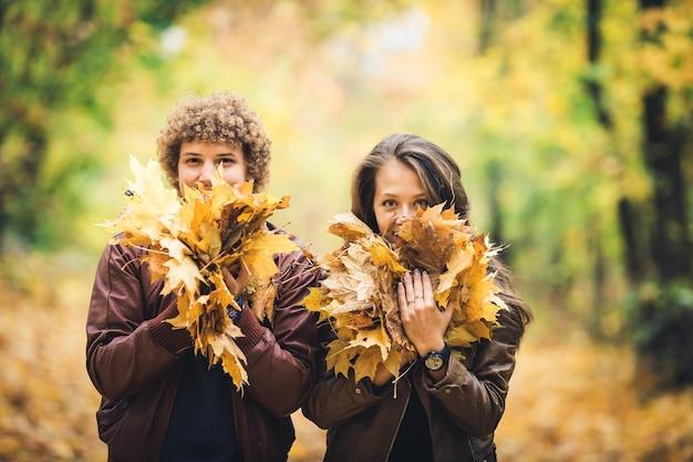 Jongen en meisje houden veel herfstesdoornbladeren in hun handen en sluiten hun gezichten