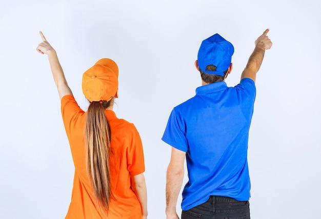 Jongen en meisje in blauwe en gele uniformen die links en rechts iets presenteren.