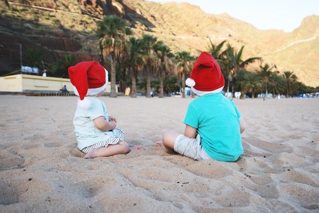 Jongen en meisje in rode kerstmutsen die plezier hebben op het oceaanzandstrand kinderen spelen op de achtergrond van de zeekust