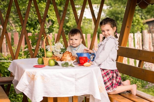 Jongen en meisje in zomerhuisje drinken thee met broodjes in de zomer