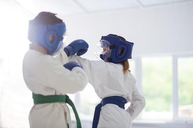 Jongen en meisje. jongen en meisje met witte kimono en beschermende helmen die vechten bij het bestuderen van vechtsporten