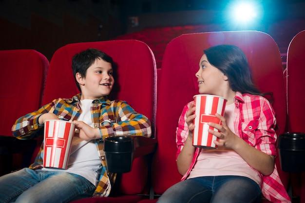 Jongen en meisje kijken naar film in de bioscoop