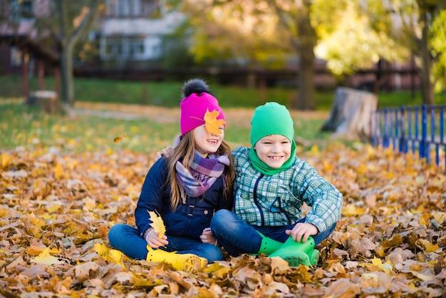 Jongen en meisje knuffelen en zitten op de herfstbladeren