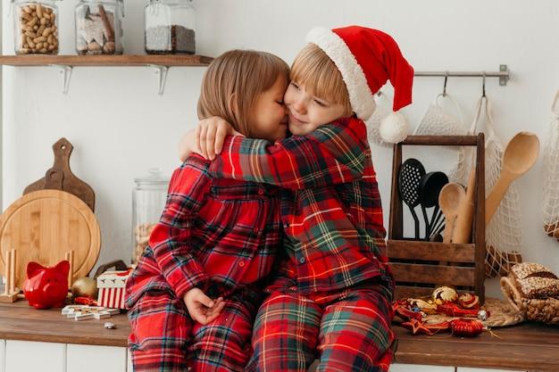 Jongen en meisje knuffelen op eerste kerstdag