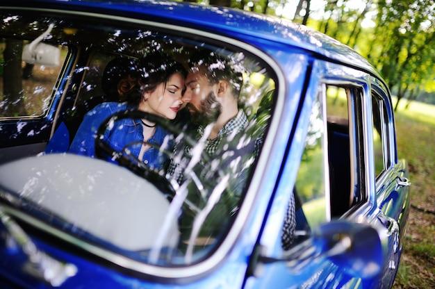 Jongen en meisje kussen in de retro auto