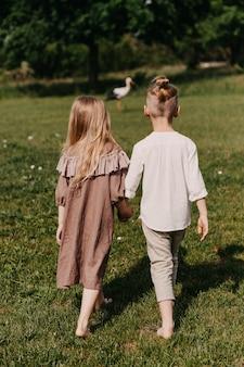 Jongen en meisje lopen op groen gras, blootsvoets