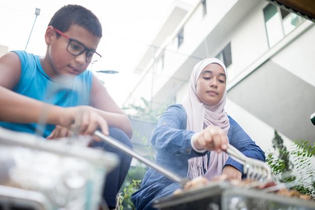 Jongen en meisje maken van barbecue