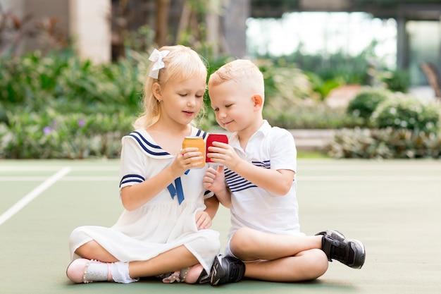 Jongen en meisje met drankje blikjes buitenshuis