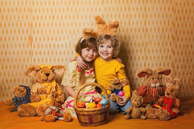 Jongen en meisje met konijnenoren zitten rond een heleboel stro en pluche hazen, vintage stijl.
