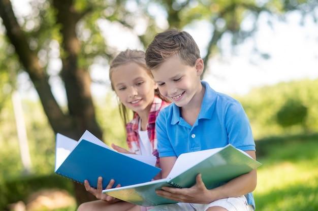 Jongen en meisje met oefenboeken in park
