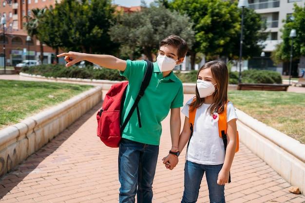 Jongen en meisje met rugzakken en maskers die naar school gaan in pandemie van het coronavirus