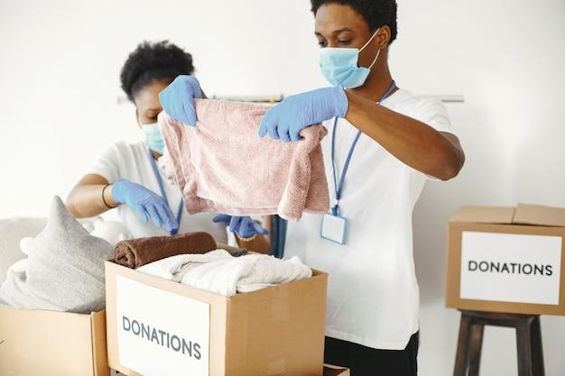 Jongen en meisje met selectievakjes. afrikaanse vrijwilligers in maskers. dozen met humanitaire hulp.
