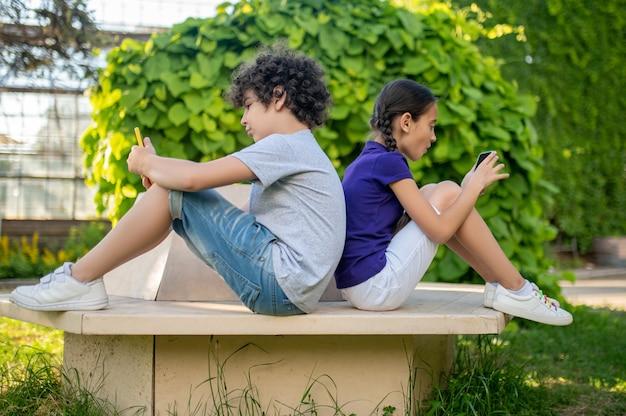 Jongen en meisje met smartphones in park