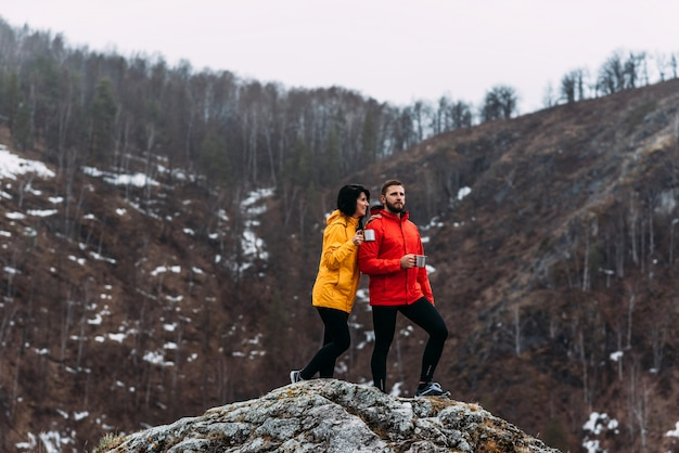 Jongen en meisje reizen in de bergen. man en vrouw drinken hete thee in de bergen. een verliefd paar koestert zich in hete thee. berg beklimmen.