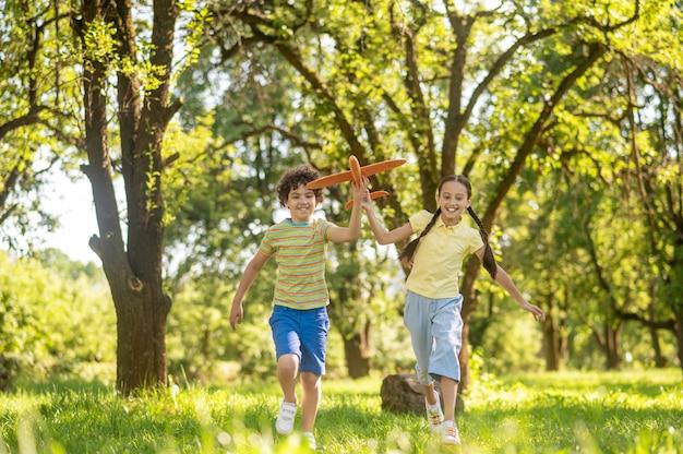 Jongen en meisje rennen met speelgoedvliegtuig