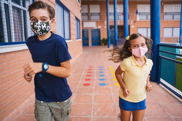 Jongen en meisje rennen op het schoolplein met gezichtsmasker tijdens covid pandemie. terug naar school tijdens de covid-pandemie