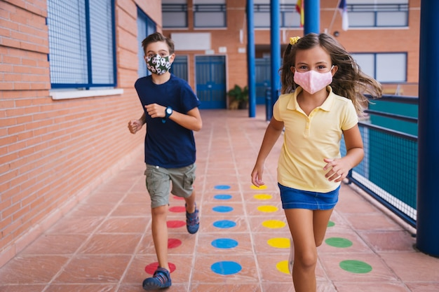 Jongen en meisje rennen op het schoolplein met gezichtsmasker tijdens covid pandemie.
