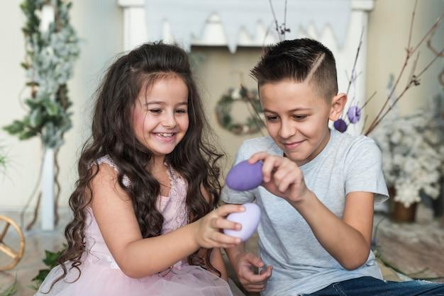 Jongen en meisje spelen met paaseieren