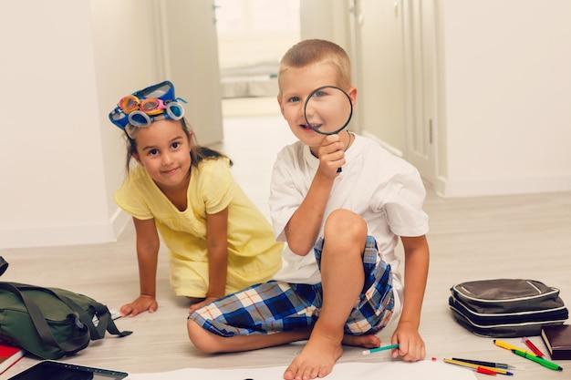 Jongen en meisje spelen met vergrootglas en glazen