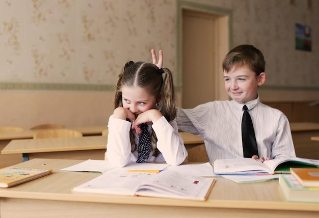 Jongen en meisje studenten genieten van zittend aan een bureau. de jongen trekt aan de staartjes van het meisje.