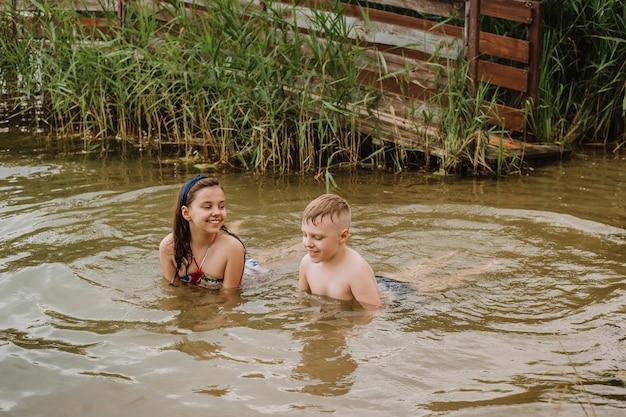 Jongen en meisje swimmimg in het meer. zomervakantie.