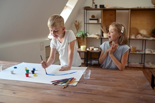Jongen en meisje tekenen met gouache aan tafel, kinderen in werkplaats. les op de kunstacademie. jonge schilders, leuke hobby, gelukkige jeugd