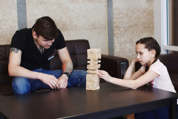Jongen en meisje tiener bouwen een toren van houten blokken game jenga op de tafel zittend op de bank