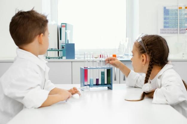 Jongen en meisje wetenschappers in het laboratorium met veiligheidsbril