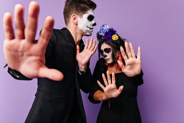 Jongen en meisje willen geen foto maken en zichzelf bedekken met hun handen. binnenportret van verlegen paar met geschilderde gezichten.