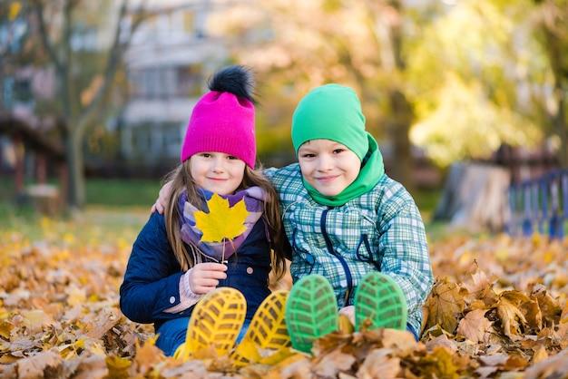 Jongen en meisje zitten tijdens wandeling in herfst regenachtig park