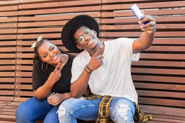 Jongen en meisje zittend op een bankje tijdens het nemen van een selfie