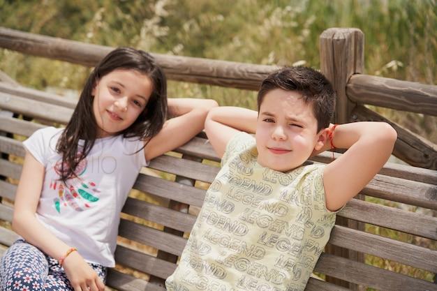 Jongen en meisje zittend op een houten bankje lachen ontspannen in het park