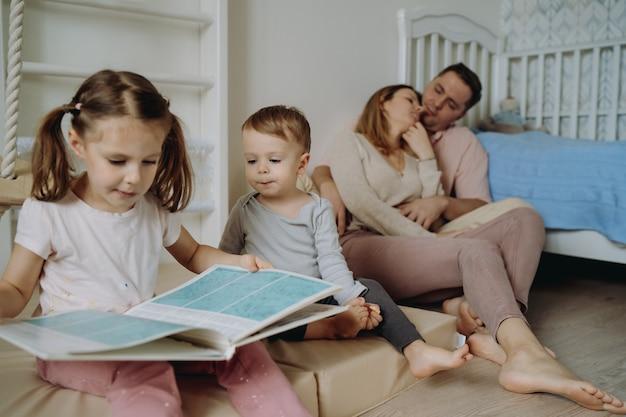 Jongen en meisjes lezen een boek in de kinderkamer ouders knuffelen op de achtergrond
