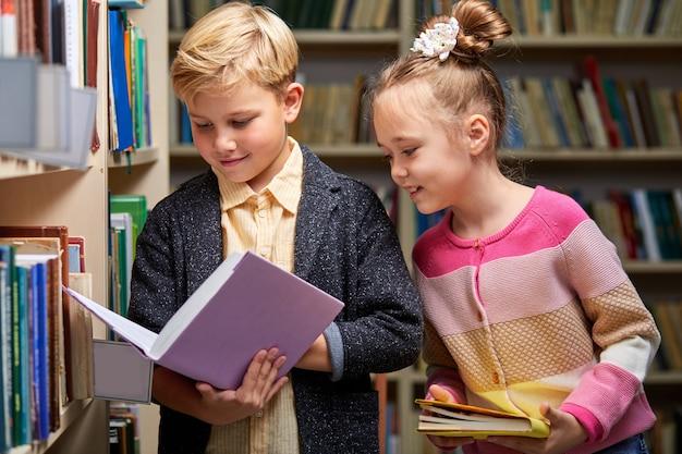 Jongen en meisjeskinderen die boeken in bibliotheek, mensenlevensstijlen en onderwijsconcept lezen. jonge vriendschap en jonge geitjesrelatie in schoolconcept