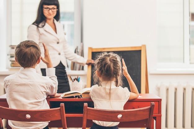 Jongen en meisjeskinderen met de leraar in de school