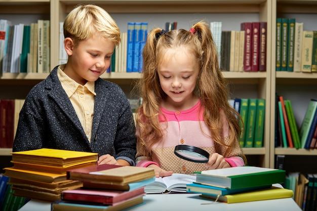 Jongen en meisjeslezingsboek in schoolbibliotheek, mensenlevensstijlen en vriend onderwijs en vriendschapsconcept. vrije tijd voor kinderen, groepsactiviteit
