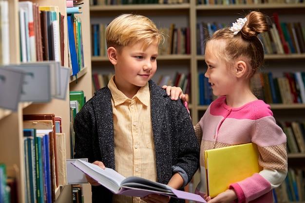Jongen en meisjeslezingsboek in schoolbibliotheek, mensenlevensstijlen en vriend onderwijs en vriendschapsconcept.